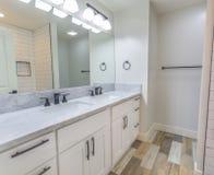Άσπρο λουτρό με το ξύλινο πάτωμα και διπλός νεροχύτης στο Σαν Ντιέγκο Καλιφόρνια Στοκ Εικόνες