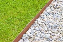 Άσπρο πάτωμα αμμοχάλικου και φρέσκος πράσινος χορτοτάπητας με τα τριφύλλια και τα σκουριασμένα σχεδιαγράμματα συγκράτησης μετάλλω στοκ εικόνα με δικαίωμα ελεύθερης χρήσης