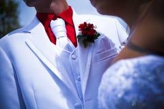 Άσπρο παλτό γαμήλιων γαμπρών με το κόκκινο λουλούδι στοκ εικόνες με δικαίωμα ελεύθερης χρήσης