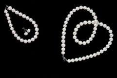 Άσπρο περιδέραιο, σκουλαρίκια και βραχιόλι μαργαριταριών που απομονώνονται στο μαύρο υπόβαθρο στοκ φωτογραφία με δικαίωμα ελεύθερης χρήσης
