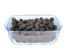 Άσπρο πιάτο γυαλιού υποβάθρου με τα βατόμουρα Στοκ Εικόνες