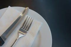 Άσπρο πιάτο δικράνων και μαχαιριών Στοκ Φωτογραφία
