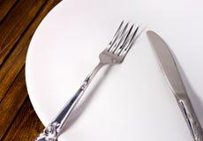 Άσπρο πιάτο δικράνων και μαχαιριών Στοκ Φωτογραφίες