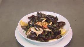 Άσπρο πιάτο με τα έτοιμα μύδια στο κρασί με το λεμόνι, τις γαρίδες και το βασιλικό Φρέσκο πιάτο εστιατορίων ατμός απόθεμα βίντεο