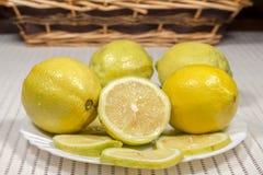 Άσπρο πιάτο με τα λεμόνια με ένα ψάθινο καλάθι στο υπόβαθρο Στοκ εικόνες με δικαίωμα ελεύθερης χρήσης