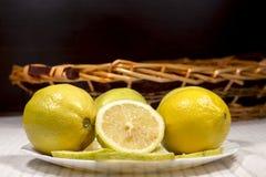 Άσπρο πιάτο με τα λεμόνια μπροστά από ένα ψάθινο καλάθι Στοκ Εικόνα