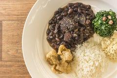 Άσπρο πιάτο με τα συστατικά του feijoada, χαρακτηριστικά τρόφιμα της Βραζιλίας στοκ εικόνες