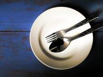 Άσπρο πιάτο με το κουτάλι και δίκρανο σε ένα ξύλινο υπόβαθρο Στοκ Φωτογραφίες