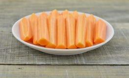 Άσπρο πιάτο με το ραβδί περικοπών του καρότου στο ξύλινο υπόβαθρο Στοκ φωτογραφία με δικαίωμα ελεύθερης χρήσης