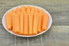 Άσπρο πιάτο με το ραβδί περικοπών του καρότου στο ξύλινο υπόβαθρο Στοκ Φωτογραφία