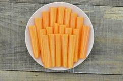 Άσπρο πιάτο με το ραβδί περικοπών του καρότου στο ξύλινο υπόβαθρο Στοκ Φωτογραφίες