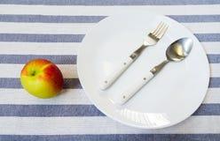 Άσπρο πιάτο με το σύνολο κουταλιών και δικράνων ανοξείδωτου που τοποθετείται έπειτα Στοκ Φωτογραφία