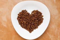 Άσπρο πιάτο μορφής καρδιών φασολιών καφέ Στοκ εικόνα με δικαίωμα ελεύθερης χρήσης