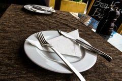 Άσπρο πιάτο πορσελάνης, μαχαίρι, δίκρανο στον πίνακα εστιατορίων οδών με ένα καφετί τραπεζομάντιλο Στοκ Εικόνες