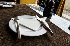 Άσπρο πιάτο πορσελάνης, μαχαίρι, δίκρανο στον πίνακα εστιατορίων οδών με ένα καφετί τραπεζομάντιλο Στοκ φωτογραφία με δικαίωμα ελεύθερης χρήσης