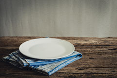 Άσπρο πιάτο σε μια πετσέτα ξύλινο tabletop Στοκ φωτογραφία με δικαίωμα ελεύθερης χρήσης