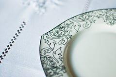 Άσπρο πιάτο στο τραπεζομάντιλο Στοκ Εικόνες
