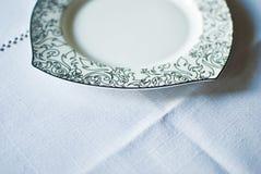 Άσπρο πιάτο στο τραπεζομάντιλο Στοκ Εικόνα