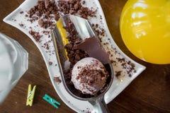 Άσπρο πιάτο των σεσουλών παγωτού σοκολάτας που ψεκάζονται με τη σοκολάτα στον ξύλινο πίνακα Στοκ φωτογραφία με δικαίωμα ελεύθερης χρήσης