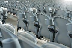 Άσπρο πλαστικό που διπλώνει τα κενά κόκκινα καθίσματα στη συναυλία ή το γήπεδο ποδοσφαίρου Στοκ Φωτογραφία