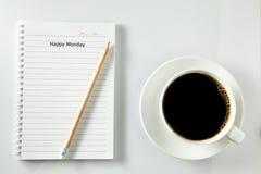 Άσπρο πρωί φλιτζανιών του καφέ στον ξύλινο πίνακα με το σημειωματάριο Στοκ Φωτογραφία