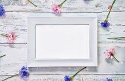 Άσπρο πρότυπο πλαισίων με τα λουλούδια στον πίνακα Στοκ Εικόνες