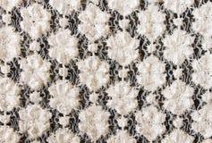 Άσπρο πλέκοντας σχέδιο λουλουδιών στο μαύρο υπόβαθρο σύστασης υφάσματος Στοκ φωτογραφία με δικαίωμα ελεύθερης χρήσης