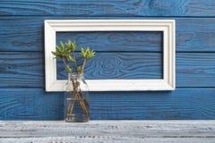 Άσπρο πλαίσιο και ένα βάζο με τους κλάδους άνοιξη ενάντια μπλε πίνακες Στοκ φωτογραφία με δικαίωμα ελεύθερης χρήσης