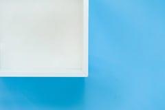 Άσπρο ράφι κιβωτίων που απομονώνεται στο μπλε υπόβαθρο Στοκ Φωτογραφία