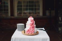 Άσπρο ρόδινο γαμήλιο κέικ με τα τριαντάφυλλα στο γραφείο στοκ φωτογραφίες