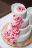 Άσπρο ρόδινο γαμήλιο κέικ με τα τριαντάφυλλα στοκ εικόνες