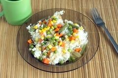 Άσπρο ρύζι με τα λαχανικά στο πιάτο πέρα από το ψάθινο χαλί Στοκ Φωτογραφίες