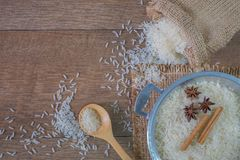 Άσπρο ρύζι στο χάλυβα κύπελλων με την ξύλινη, τοπ άποψη κουταλιών στοκ εικόνα
