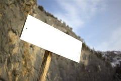 Άσπρο σημάδι πινάκων περιπέτειας το κενό στα βουνά bokeh βλέπει, στους ηλιόλουστους τουρίστες αλπινισμού αναρρίχησης βράχου ημέρα Στοκ εικόνα με δικαίωμα ελεύθερης χρήσης