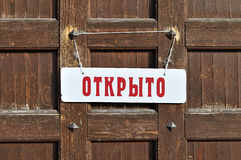 Άσπρο σημάδι με την επιγραφή σε ρωσικά εμείς ` σχετικά με ανοικτό στην καφετιά ξύλινη πόρτα με τα παλαιά καρφιά μετάλλων - αναδρο Στοκ εικόνα με δικαίωμα ελεύθερης χρήσης