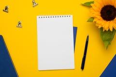Άσπρο σημειωματάριο με το μπλε σημειωματάριο και μάνδρα στο κίτρινο υπόβαθρο στοκ εικόνα με δικαίωμα ελεύθερης χρήσης