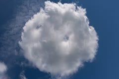 Άσπρο στρογγυλό σύννεφο, που διαμορφώνεται όπως το κουλούρι, στο μπλε ουρανό στοκ εικόνες