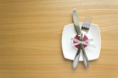 Άσπρο πιάτο με το δίκρανο και μαχαίρι σε έναν ξύλινο πίνακα Στοκ Εικόνες