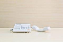 Άσπρο τηλέφωνο κινηματογραφήσεων σε πρώτο πλάνο, τηλέφωνο γραφείων στο θολωμένο ξύλινο γραφείο και κατασκευασμένο υπόβαθρο τοίχων Στοκ εικόνες με δικαίωμα ελεύθερης χρήσης