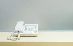 Άσπρο τηλέφωνο κινηματογραφήσεων σε πρώτο πλάνο, τηλέφωνο γραφείων στο θολωμένο ξύλινο γραφείο και παγωμένο υπόβαθρο τοίχων γυαλι Στοκ Φωτογραφίες