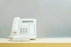 Άσπρο τηλέφωνο κινηματογραφήσεων σε πρώτο πλάνο, τηλέφωνο γραφείων στο θολωμένο ξύλινο γραφείο και παγωμένο υπόβαθρο τοίχων γυαλι Στοκ Εικόνες