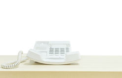 Άσπρο τηλέφωνο κινηματογραφήσεων σε πρώτο πλάνο, τηλέφωνο γραφείων στο θολωμένο ξύλινο γραφείο στην αίθουσα συνεδριάσεων κάτω από Στοκ Εικόνα