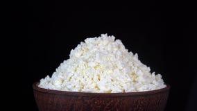 Άσπρο τυρί εξοχικών σπιτιών στο μαύρο υπόβαθρο Περιστρέφεται το κύπελλο με το φρέσκο τυρί εξοχικών σπιτιών φιλμ μικρού μήκους