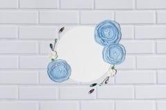 Άσπρο υπόβαθρο κύκλων με τα μπλε χειροποίητα λουλούδια βατραχίων Στοκ εικόνα με δικαίωμα ελεύθερης χρήσης