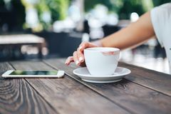 Άσπρο φλιτζάνι του καφέ με το κραγιόν Στον πίνακα ένα φλιτζάνι του καφέ και ένα τηλέφωνο στοκ φωτογραφία