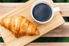 Άσπρο φλυτζάνι καφέ και γαλλικό Croissant στον ξύλινο πίνακα στον κήπο Στοκ Εικόνα