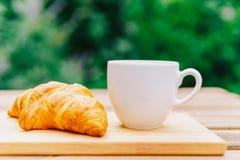 Άσπρο φλυτζάνι καφέ και γαλλικό Croissant στον ξύλινο πίνακα στον κήπο Στοκ φωτογραφία με δικαίωμα ελεύθερης χρήσης