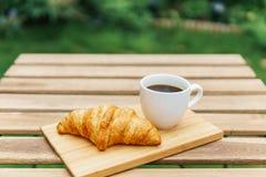 Άσπρο φλυτζάνι καφέ και γαλλικό Croissant στον ξύλινο πίνακα στον κήπο Στοκ Φωτογραφία