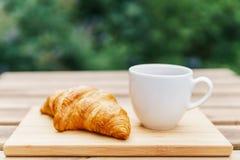 Άσπρο φλυτζάνι καφέ και γαλλικό Croissant στον ξύλινο πίνακα στον κήπο Στοκ Εικόνες