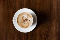 Άσπρο φλυτζάνι καφέ στον ξύλινο πίνακα γραφείων/κανένας Στοκ εικόνες με δικαίωμα ελεύθερης χρήσης
